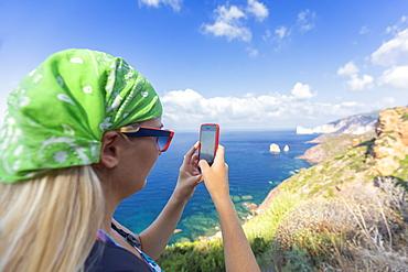 A tourist takes a photo with smartphone, Nebida, Iglesias, Sud Sardegna province, Sardinia, Italy, Mediterranean, Europe
