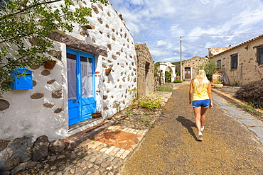 Young girl walks in a fishing village, Is Loccis Santus, San Giovanni Suergiu, Sud Sardegna province, Sardinia, Italy, Mediterranean, Europe