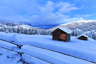 Old snow-covered huts during twilight, Erbe Pass, Funes Valley, Sudtirol (South Tyrol), Dolomites, Italy, Europe