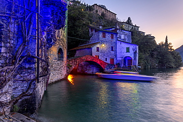 Boat in motion under the illuminated Nesso bridge, Lake Como, Lombardy, Italian Lakes, Italy, Europe