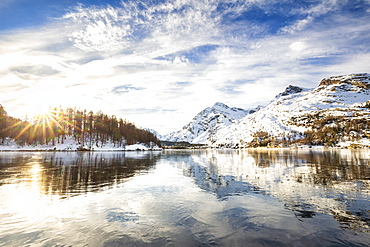 The sun illuminates the icy surfaces of Lake Sils, Engadine Valley, Graubunden, Swiss Alps, Switzerland, Europe