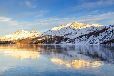 Mountains illuminated by sun at sunset reflected on the icy surfaces of Lake Sils, Engadine, Graubunden, Switzerland, Europe
