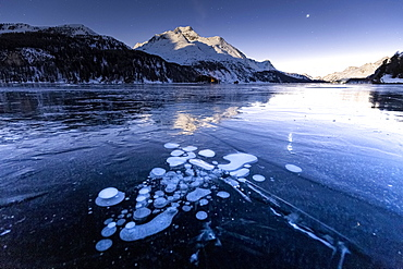 Methane bubbles in the icy surface of the lake with snowy peak illuminated by moonlight, Sils, Engadine Valley, Graubunden, Swiss Alps, Switzerland, Europe
