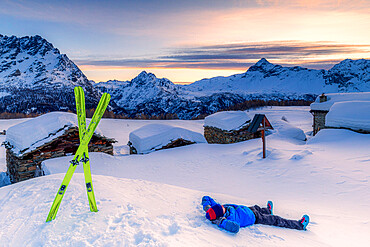 Young skier relaxes in the snow with view of the small village at sunrise, Valmalenco, Valtellina, Lombardy, Italy, Europe