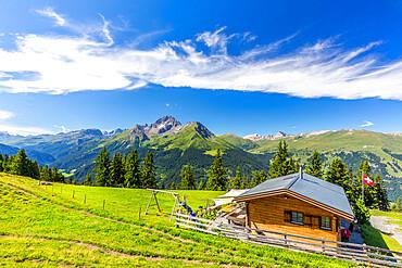 Alpine hut with Swiss flag beneath stunning clouds, Urses, Surselva, Graubunden, Switzerland, Europe