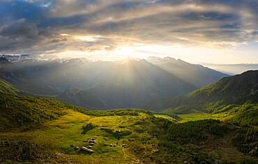 Sun filters between clouds at sunrise with illuminated pasture, Valmalenco, Valtellina, Lombardy, Italy, Europe