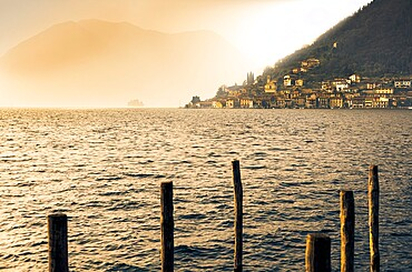Light in the fog illuminates Peschiera Maraglio village, Monte Isola, Lake Iseo, Brescia province, Lombardy, Italian Lakes, Italy, Europe