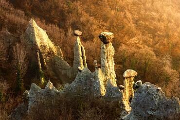 Sunlight illuminates earth pyramids (rock chimneys) of Zone, Zone, Brescia province, Lombardy, Italy, Europe