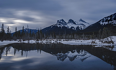 Canadian Rockies on a gloomy day, showing The Three Sisters over lake reflection, Alberta, Canada, North America