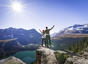 Hiker couple at the Alpine circuit trail looking down the Lake O'Hara, Yoho National Park, UNESCO World Heritage Site, Canadian Rockies, British Columbia, Canada, North America