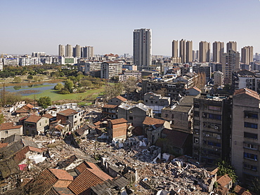 Tall buildings rise behind torn down old apartment buildings, Jingzhou, Hubei, China, Asia