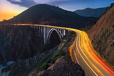 Sunset over Bixby Creek Bridge and car trail lights, Big Sur, California, United States of America, North America