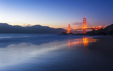 Soft flowing water reflects the beautiful Golden Gate Bridge from Baker Beach, San Francisco, California, United States of America, North America