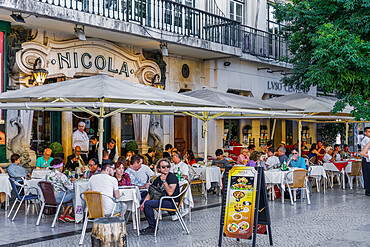 Lisbon, Portugal historic cafe Nicola entrance with art deco facade & seated customers at outdoor tables in Rossio square.