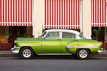 Green vintage American car parked in front of cafe, Cienfuegos, UNESCO World Heritage Site, Cuba, West Indies, Caribbean, Central America