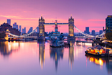 Sunrise view of HMS Belfast and Tower Bridge with Canary Wharf in background, London, England, United Kingdom, Europe