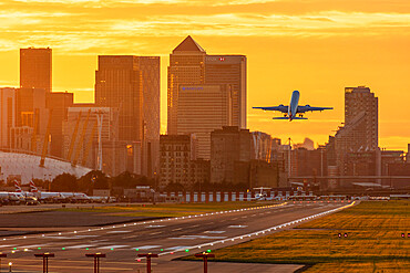 Aircraft taking off from London City Airport at sunset, with Canary Wharf and O2 Arena in background.