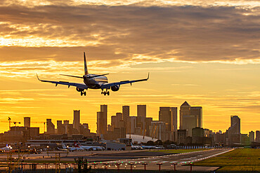 Aircraft landing at London City Airport at sunset, with Canary Wharf and O2 Arena in background.