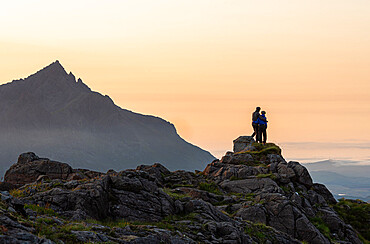 A couple standing on a rocky peak watching a mountain sunset on Skye with Sgurr nan Gillean in background