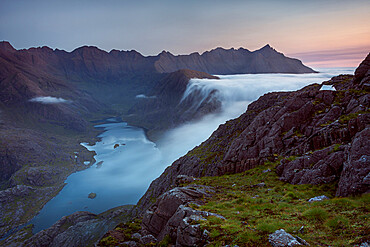 Sunrise at a Wild camp on the hills above Loch Coruisk on Skye with a cloud inversion flooding into the glen below