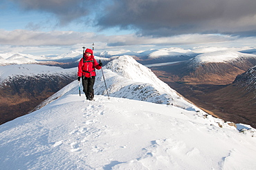 A female walker approaching the summit of Stob Dubh on Buchaille Etive Beag on a crisp winter day, Highlands, Scotland, United Kingdom, Europe