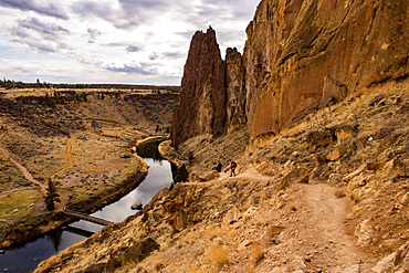 Two hikers descend a path to the river by some large rock formations, Oregon, United States of America, North America