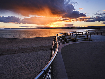 Under dramatic coloured clouds, the sun sets in line with railings on the slipway at the RNLI station, Exmouth, Devon, England, United Kingdom, Europe