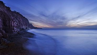 Receding wave beneath cliffs at the picturesque seaside town of Sidmouth, Devon, England, United Kingdom, Europe