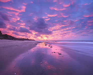 Intensely coloured and mirrored dawn sky looking towards Orcombe Point, Exmouth, Devon, England, United Kingdom, Europe