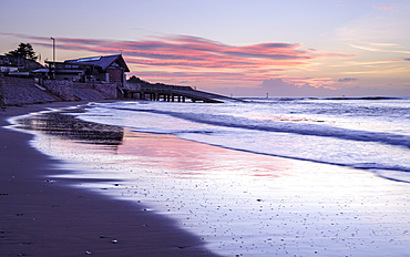 Tranquil dawn with the RNLI Station reflected in the wet beach, Exmouth, Devon, England, United Kingdom, Europe