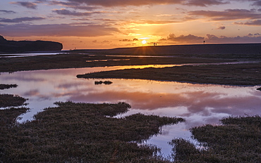 Dogwalkers have a sunrise chat with perfect reflections on the River Otter at Budleigh Salterton, Devon, England, United Kingdom, Europe