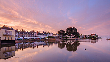 Soft dawn sky over riverside properties with a mirror calm River Exe at Topsham, Devon, UK