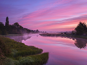 Dawn sky and rising mist from a mirror calm River Clyst at Topsham, Devon, England, United Kingdom, Europe