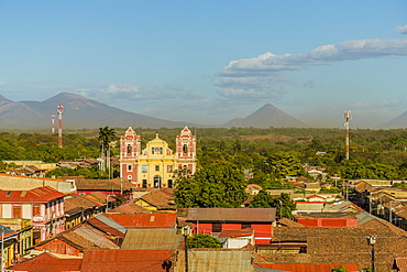 A view over the terracotta rooftops, of the colourful church of El Calvario, Leon, Nicaragua, Central America