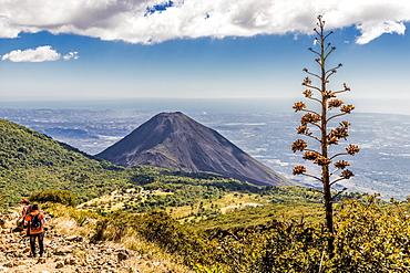 A view of Volcano Izalco and a hiker from Volcano Santa Ana (Ilamatepec ) in Santa Ana, El Salvador, Central America