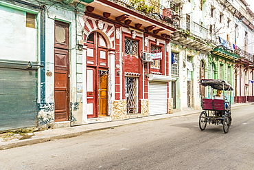 A vintage cycle rickshaw passing beautiful local architecture in Havana, Cuba, West Indies, Caribbean, Central America