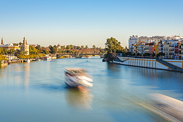 Long exposure of Betis Street in Triana and Guadalquivir River and the Torre del Oro on the left bank in late afternoon, Seville, Andalucia, Spain, Europe