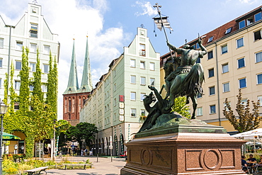 Nikolaiviertel (Nicholas Quarter) at sunset near Alexander Platz with statue of St. George Slaying The Dragon and church spires, Berlin, Germany, Europe