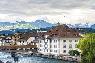 Historic old buildings with Spreuer wooden bridge on the Reuss and mountains in the background, Lucerne, Switzerland, Europe