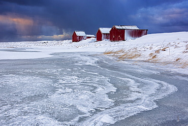 Dramatic sky over typical fishermen houses called Rorbu in winter, Eggum, Lofoten Islands, Arctic, Norway, Europe