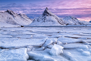 Snow covered steep mountain with frozen river on Lofoten Islands, Arctic, Norway, Europe