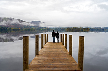 A couple standing on Ashness Pier Landing Jetty, Derwentwater, Keswick, Lake District National Park, UNESCO World Heritage Site, Cumbria, England, United Kingdom, Europe
