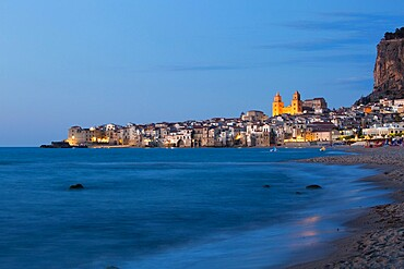 View along shore to the illuminated town and UNESCO listed Arab-Norman cathedral, dusk, Cefalu, Palermo, Sicily, Italy