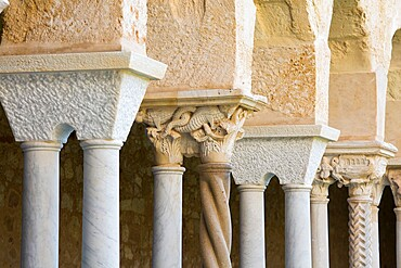 Row of columns and finely carved capitals in cloister of the UNESCO listed Arab-Norman cathedral, Cefalu, Palermo, Sicily, Italy