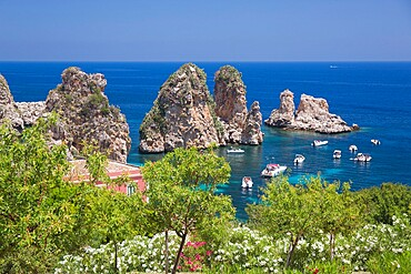 View from hillside over tranquil cove to the Faraglioni, a series of offshore rock stacks, Scopello, Trapani, Sicily, Italy, Mediterranean, Europe