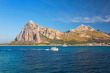 View across the bay to Monte Monaco and Pizzo di Sella, small boat returning to port, San Vito Lo Capo, Trapani, Sicily, Italy, Mediterranean, Europe