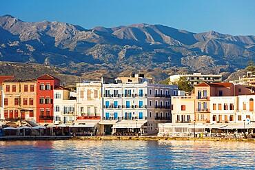 View across the Venetian Harbour to colourful waterfront buildings beneath the Lefka Ori, Hania (Chania), Crete, Greek Islands, Greece, Europe