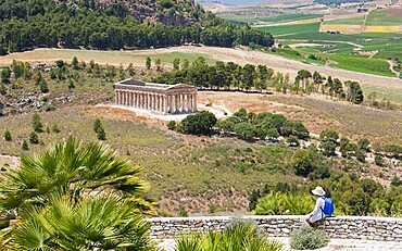 Visitor admiring view over the magnificent Doric temple at the ancient Greek city of Segesta, Calatafimi, Trapani, Sicily, Italy, Mediterranean, Europe