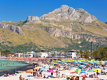 View across colourful crowded beach to the rugged slopes of Pizzo di Sella, San Vito Lo Capo, Trapani, Sicily, Italy, Mediterranean, Europe