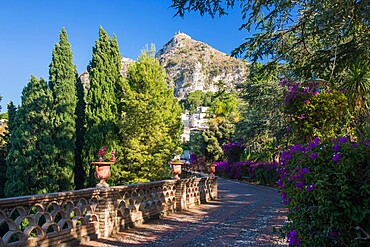 View along footpath in the gardens of the Villa Comunale, Saracen castle visible on hilltop, Taormina, Messina, Sicily, Italy